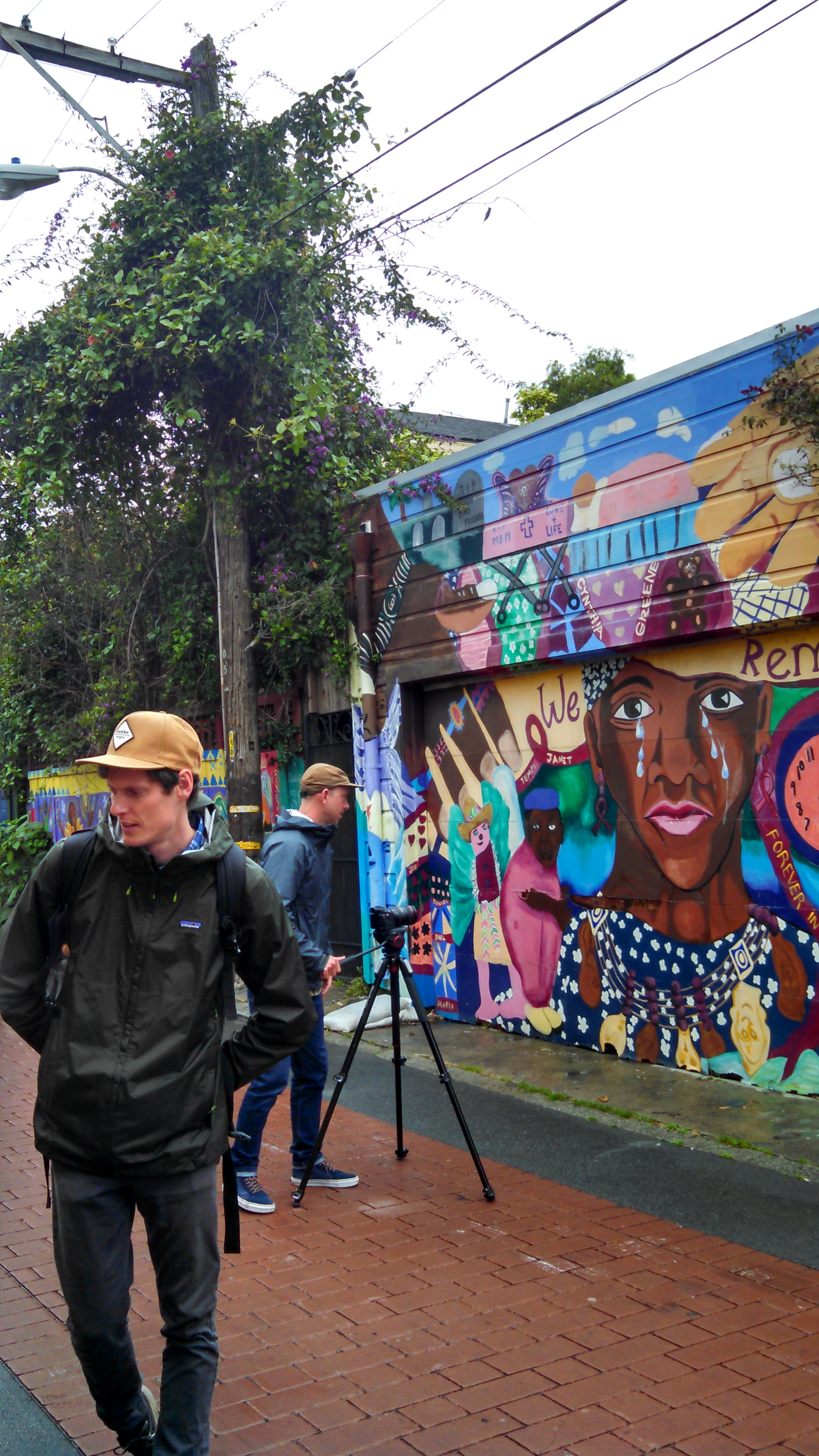Plus M Productions filming in Legal Services For Children's mural in Balmy Alley.
