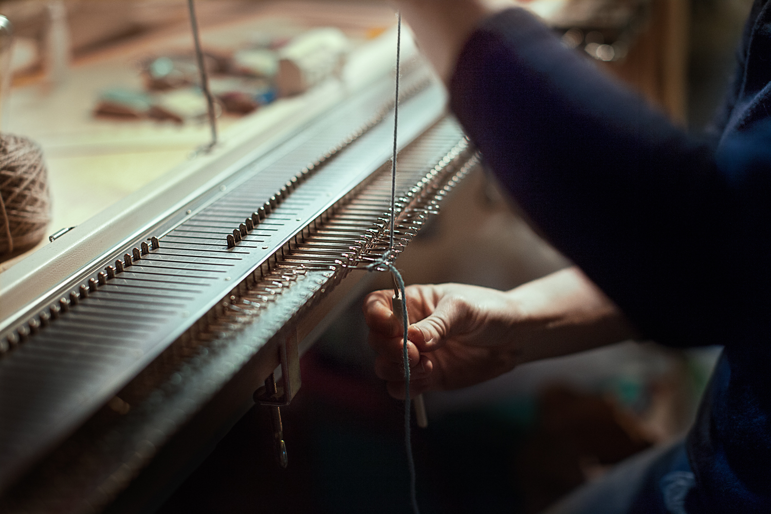 image of hands weaving on a loom