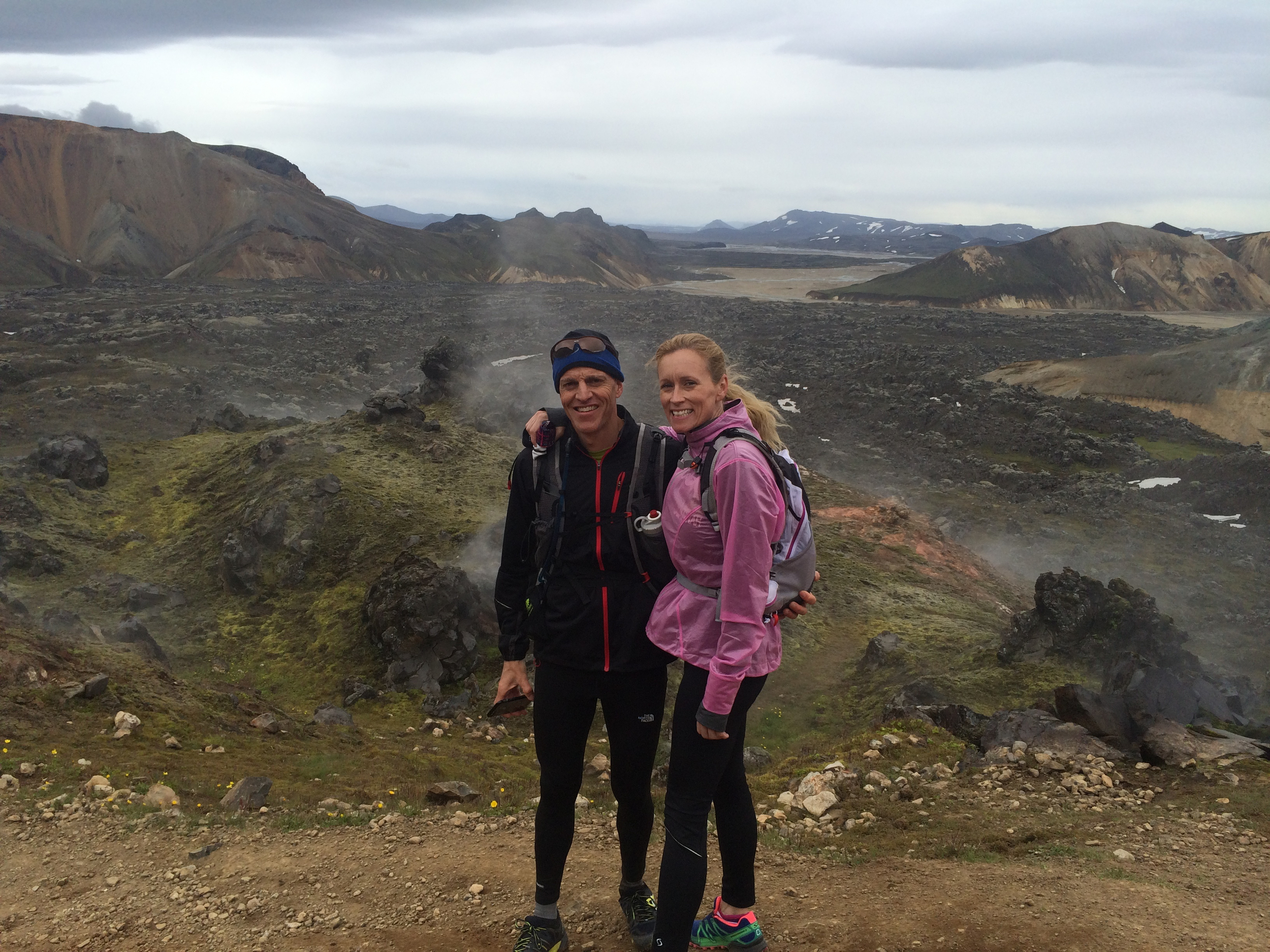 Two lovers getting a rest from running, standing in front of a lava field and a steam.