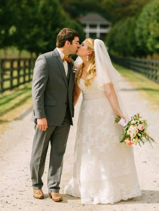bride and groom kissing by fence row