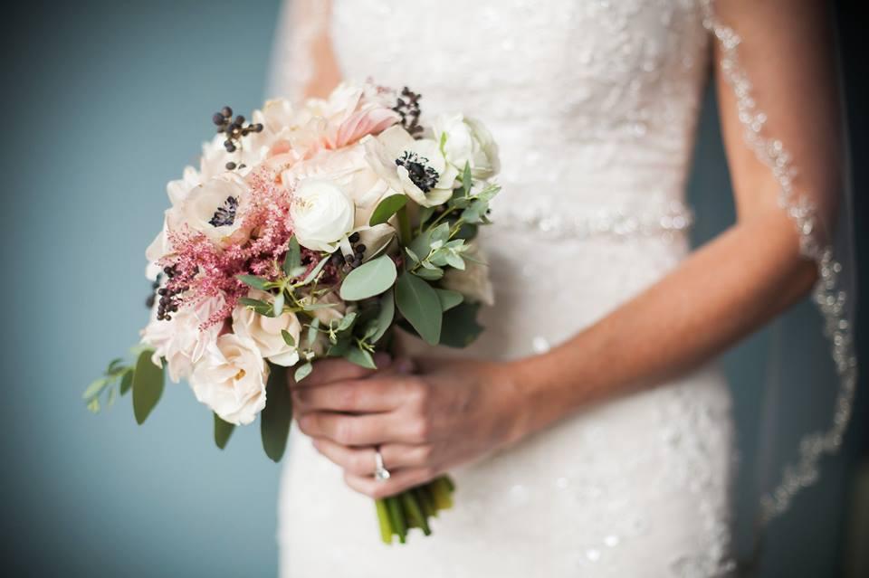 bride holding bouquet blush white
