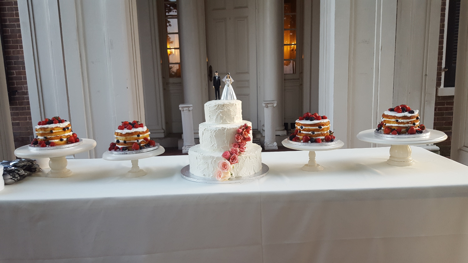 Cake display with 5 cakes.  A 3 tier wedding cake with pink flowers and 4 naked cakes with fruit.