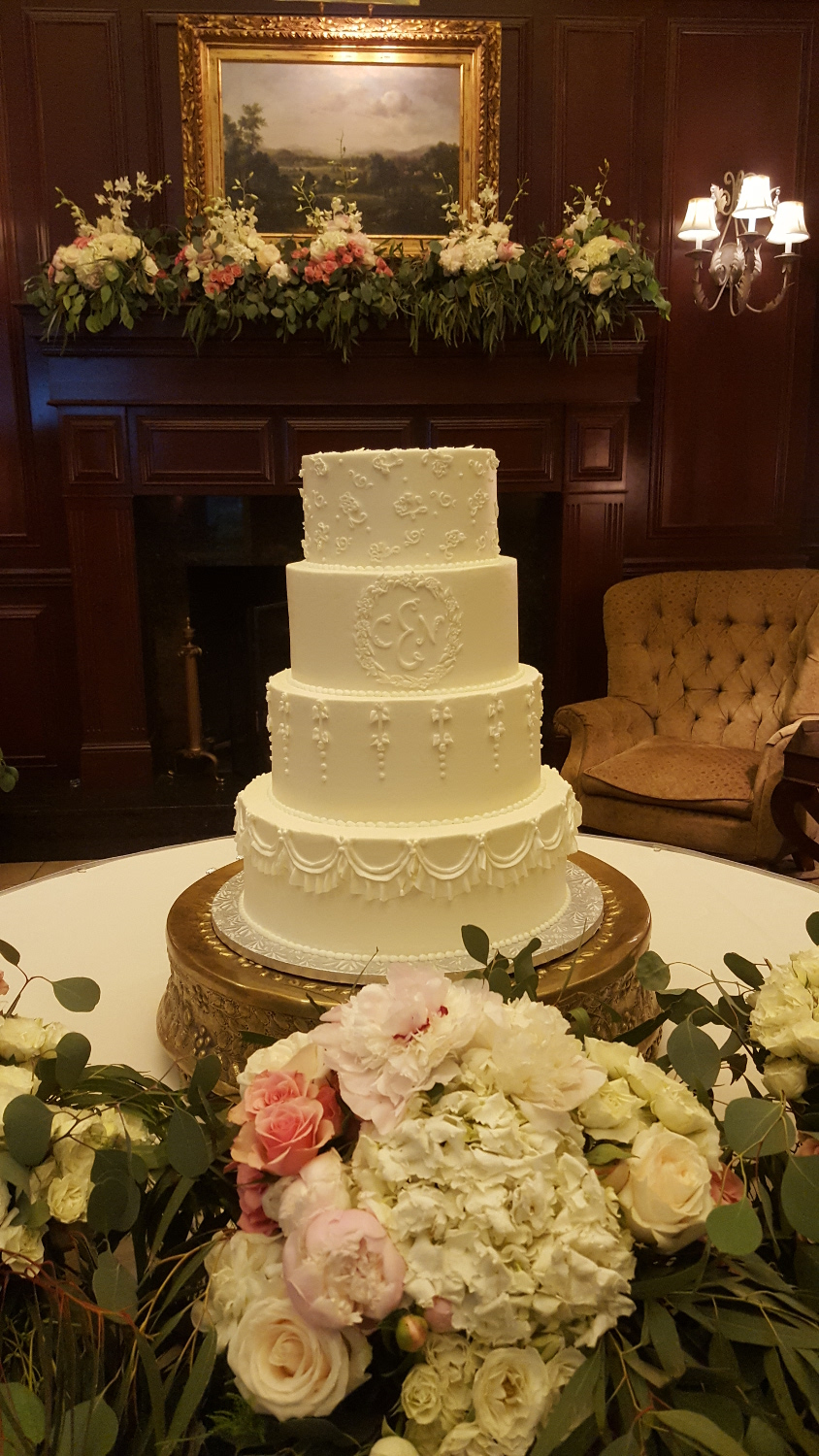 4 tier white wedding cake with intricate icing.
