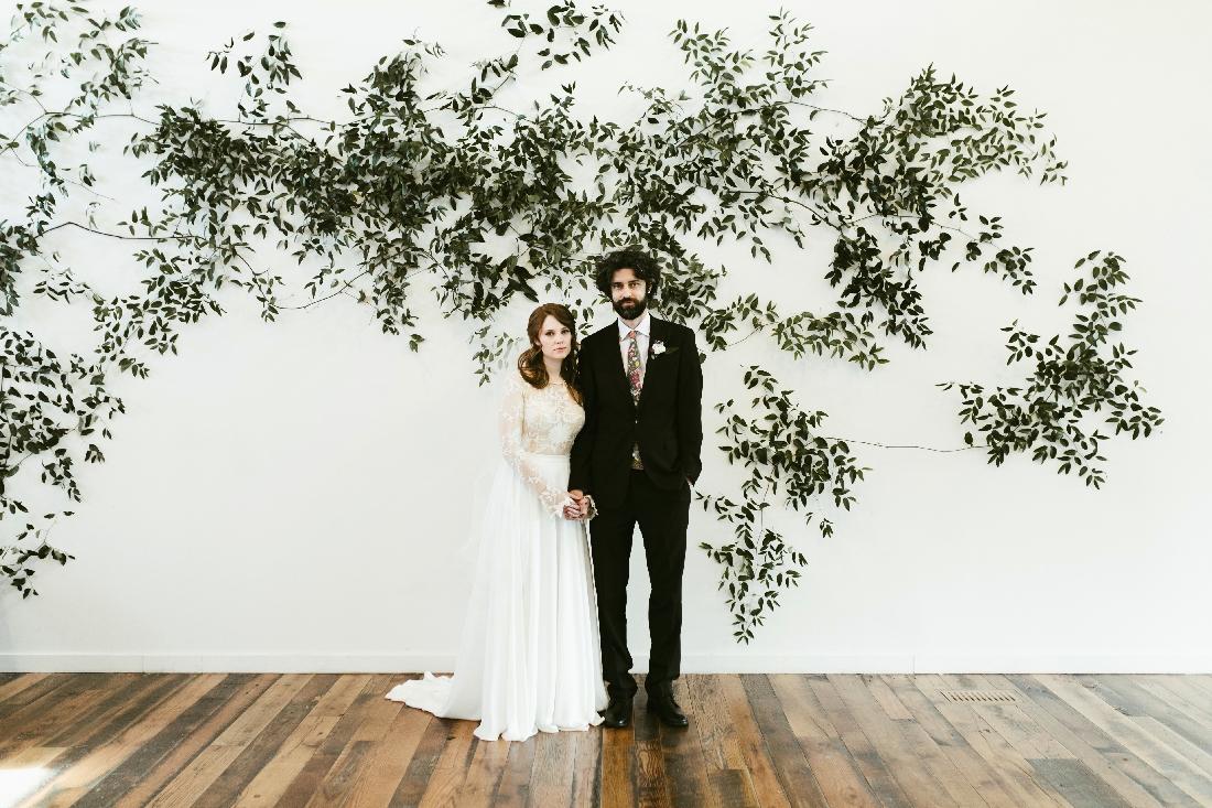 bride and groom greenery wall.jpeg