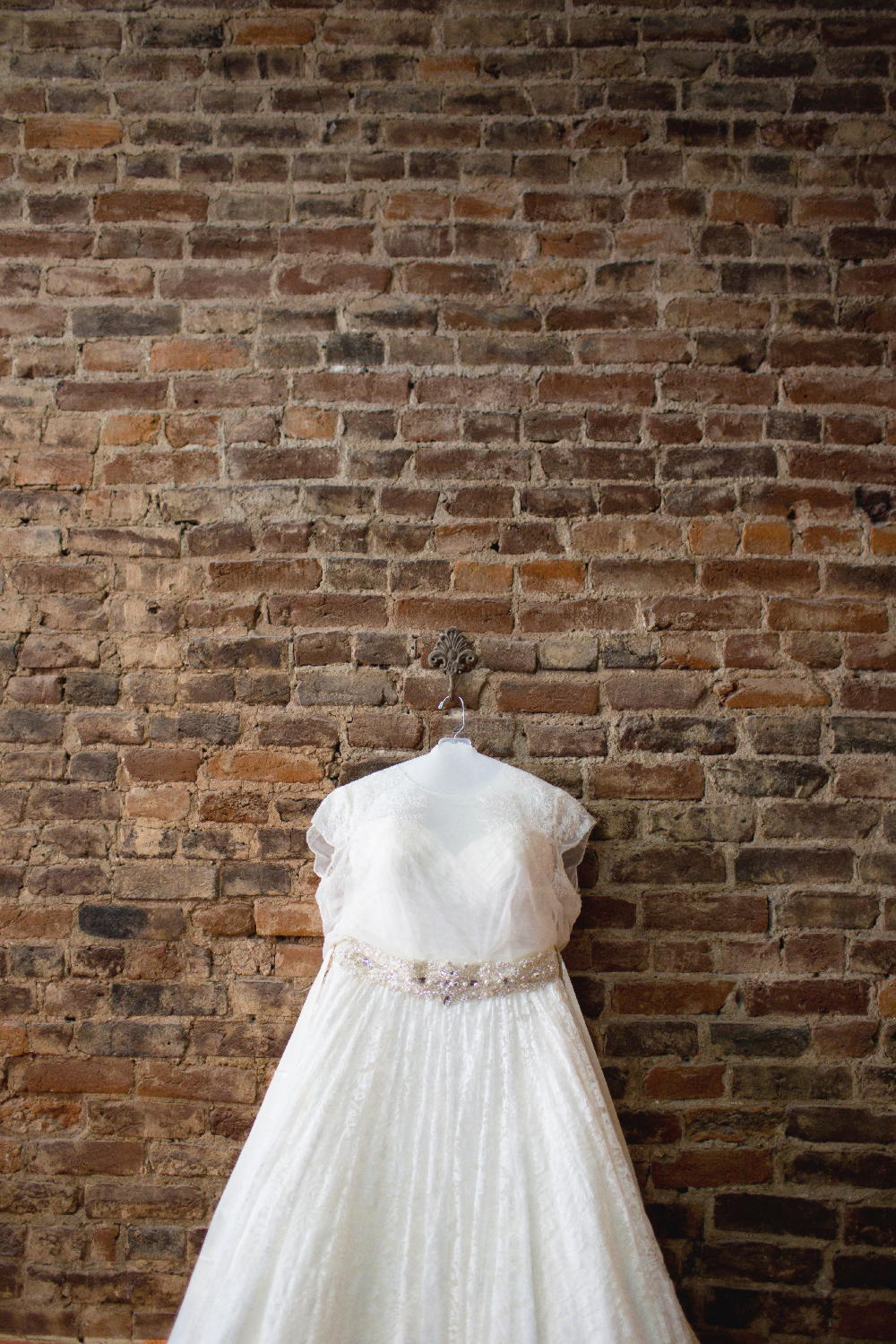 wedding dress brick wall.jpg