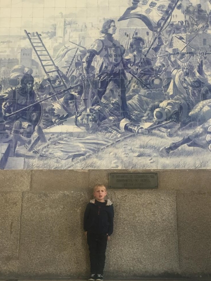 The tiled walls of the S. Bento train station tell the story of the city. Here our Henry poses in front of a mural of Prince Henry the Navigator.