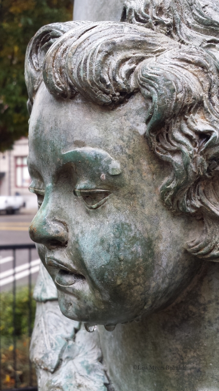 Face of putto on patina'd statue, in Tacoma's antique row district