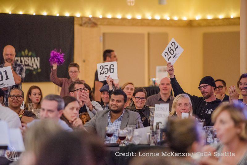 Artists raise auction paddles at 2018 CoCA Art Auction. Photo credit: Lonnie Mckenzie/CoCA