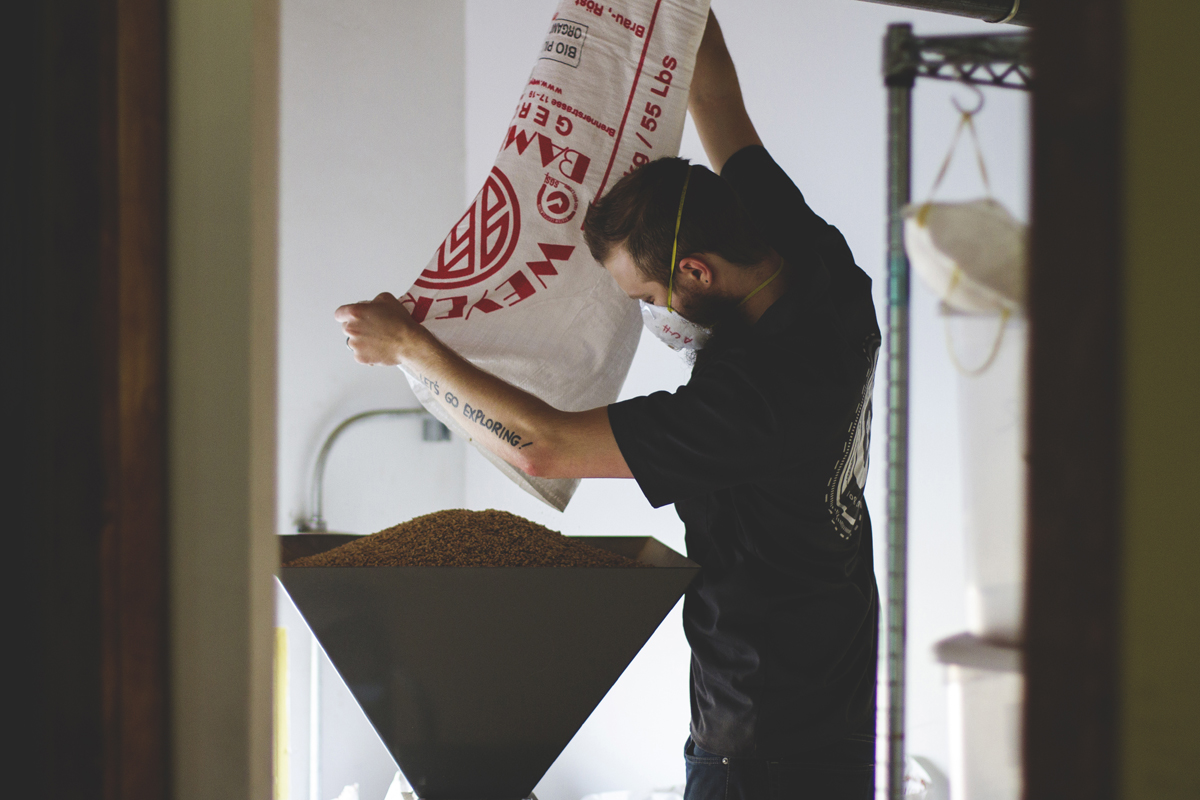 Brewer Austin Hutton pours malt into the grist mill.