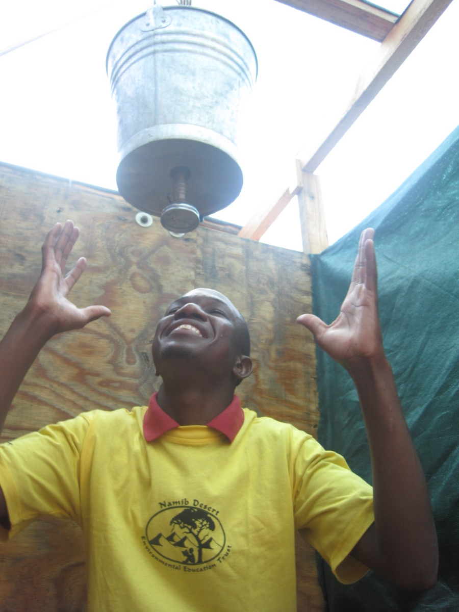 A staff member models the bucket showers