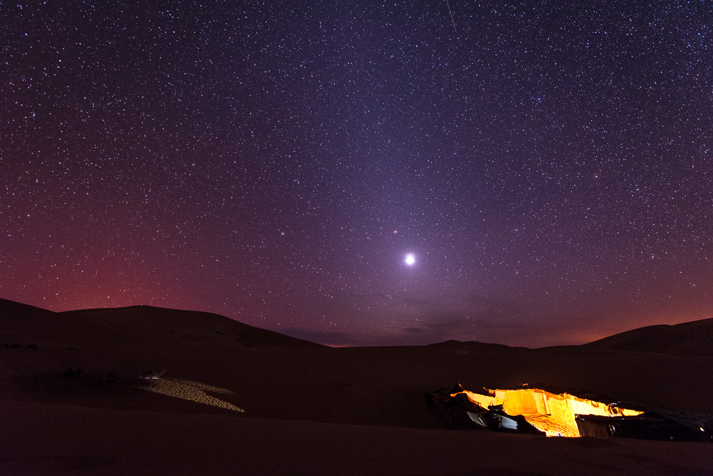 A bright Venus shines amongst the stars over a Berber camp in the Sahara Desert.