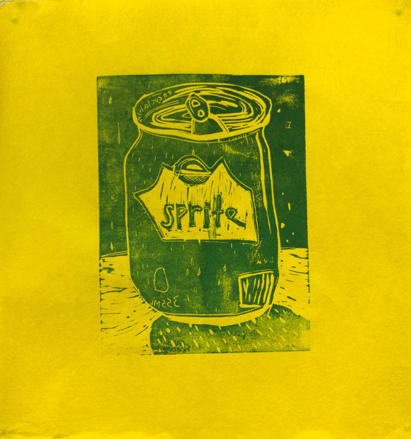 """Nubeya Curley,12 years old, 8.5x8.5"""", linocut  """"I made the Sprite can because it's my favourite pop. Right now there are no more Sprites left in Cape Dorset, it's been one week now. I am forced to drink grape crush. Many people drink pop, but they never used to have pop back in the day. In the early days of pop they used to pay 10 cents per pop and they had to share because there wasn't much money in town. Now most people drink five pops a day and they cost $2.10 per pop.""""  In the permanent collection of Jimmy Manning"""