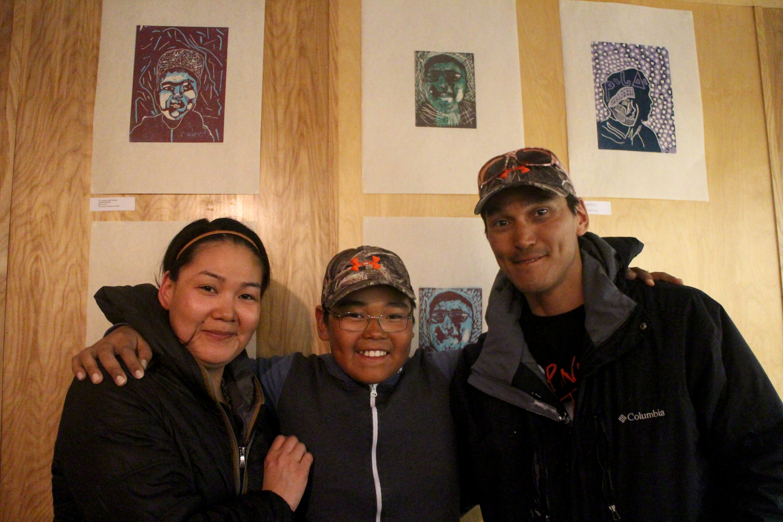 The Taukie Family: Johnnybou in the middle with his two-layer linocut self-portrait behind him.