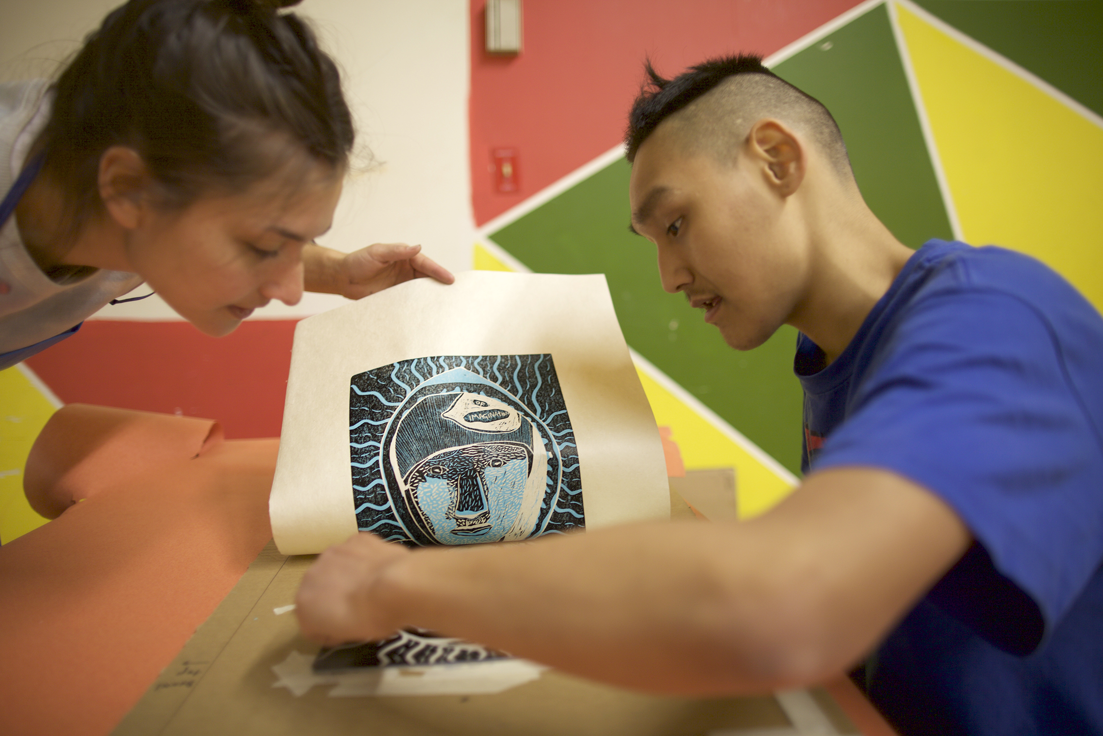 Facilitator Alexa and Cie add ink while printing the last layer of his two-layer linocut self-portrait