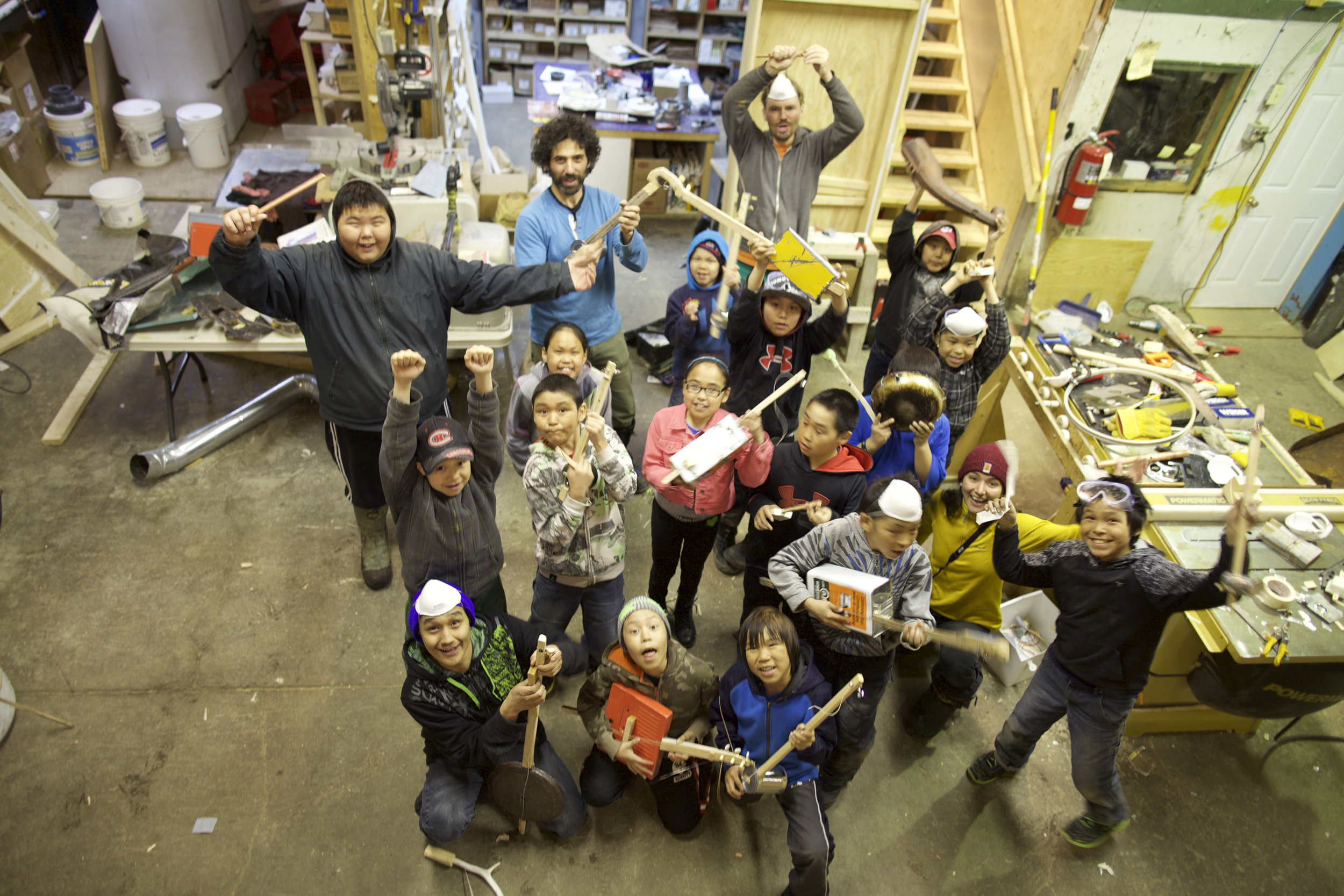 Some of the youth completing their instruments made from found materials in the dump, the burned down high school, and animal bones from the land.