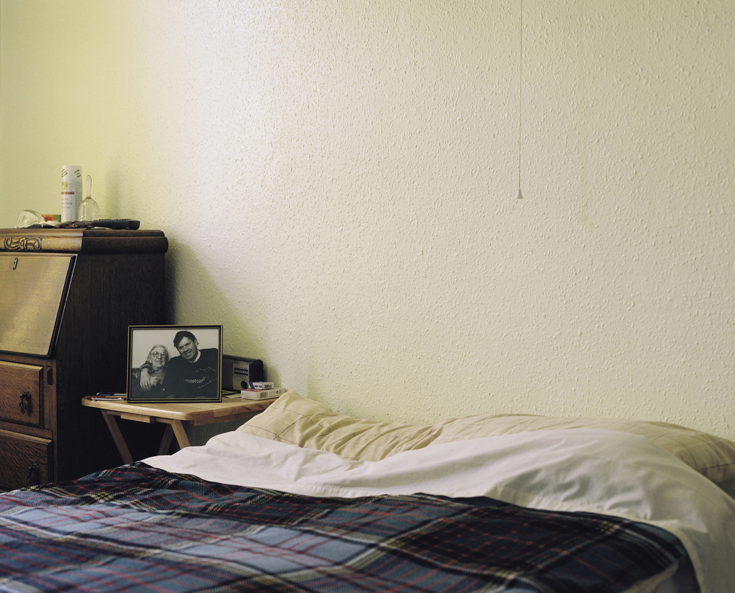 A photograph of David with his mother sits beside his bed, 2009    Project Info