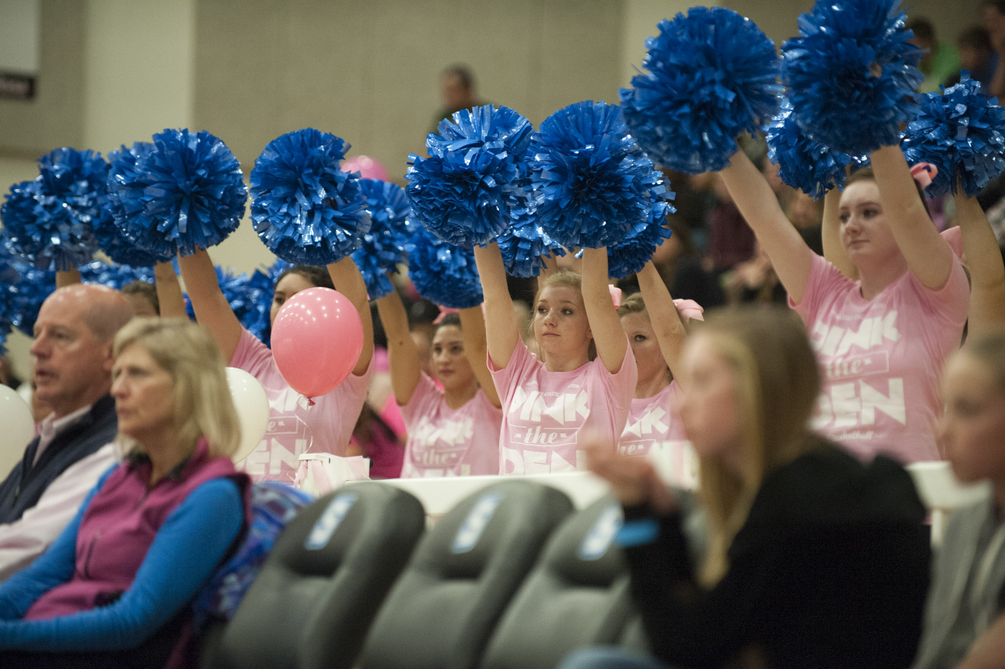 """STAR // Connor Gibson   Left: Junior Emilee Osagiede wrestles for possession of the ball. Right: Cheerleaders were court side wearing their """"Pink the Den"""" shirts."""
