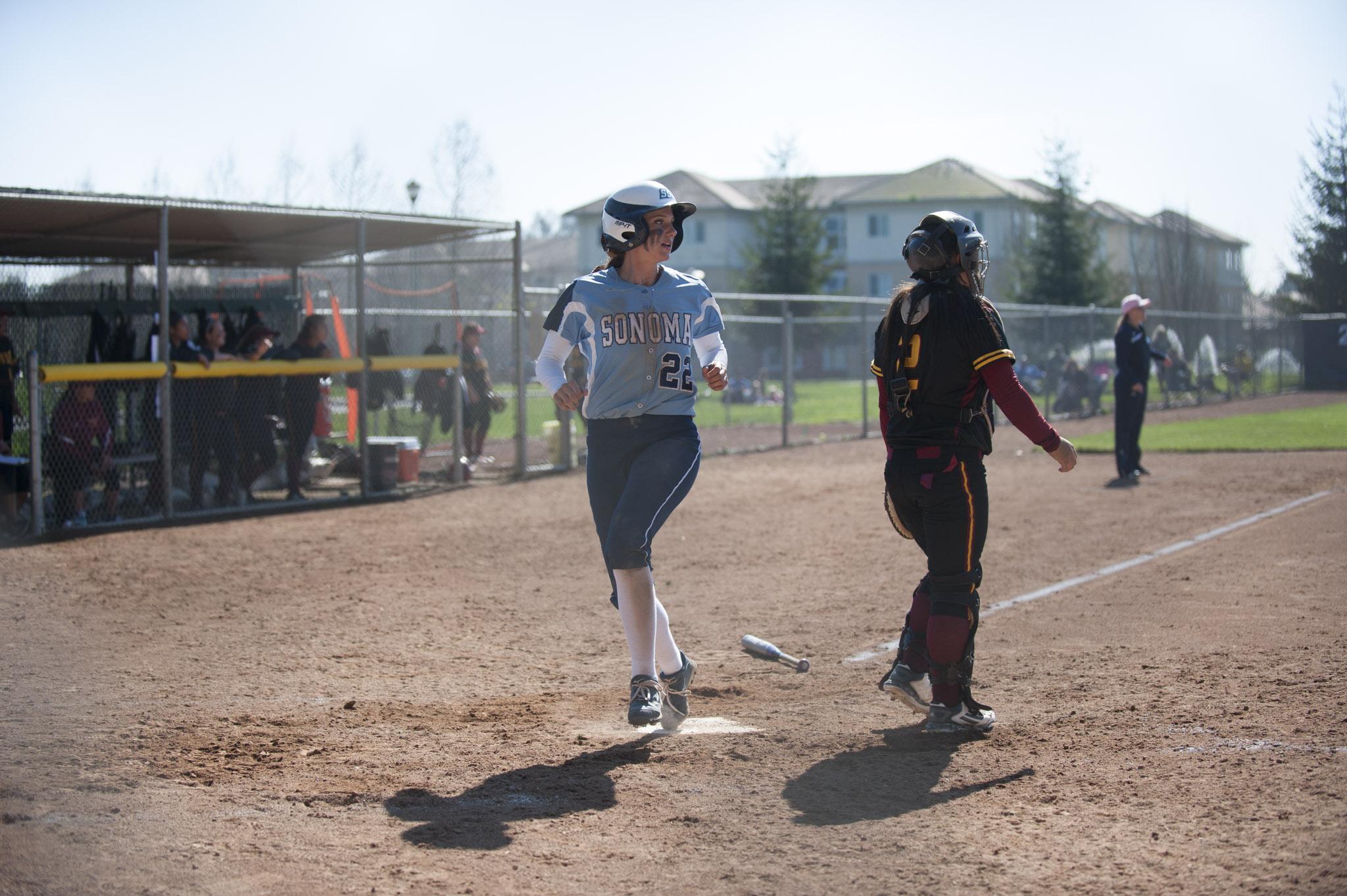 STAR // Connor Gibson   Senior Holli Brown crosses the plate.Junior Amanda Llerena (8) and senior Amanda Rosetta (16) keep it light on the field.
