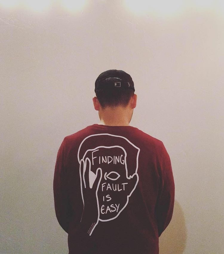 """Senior Jacob Rosales poses with his Face-Palmer sweatshirt that reads """"Finding Fault is Easy."""" Courtesy of Jacob Rosales."""