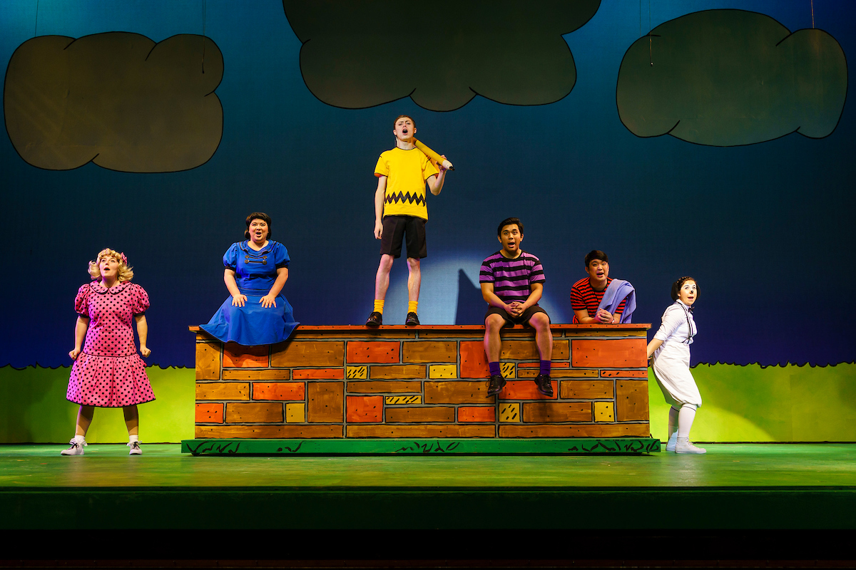 """Cast members [left to right] Hailey Patrick, Anna Leach, Noah Evans, Brandon Matel, Matthew Adiao and Emily Rice sing their hearts out in 2018's production of """"You're a Good Man, Charlie Brown."""" (COURTESY // James Wirth)"""
