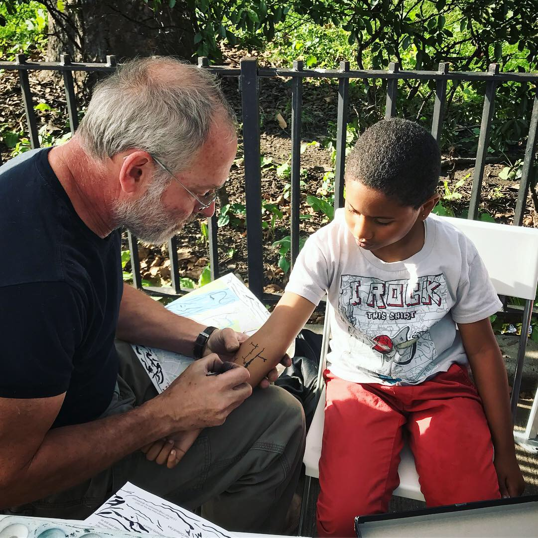 Bob Braine paints a historical map of Tibbetts Brook on a young resident of Marble Hill in September.