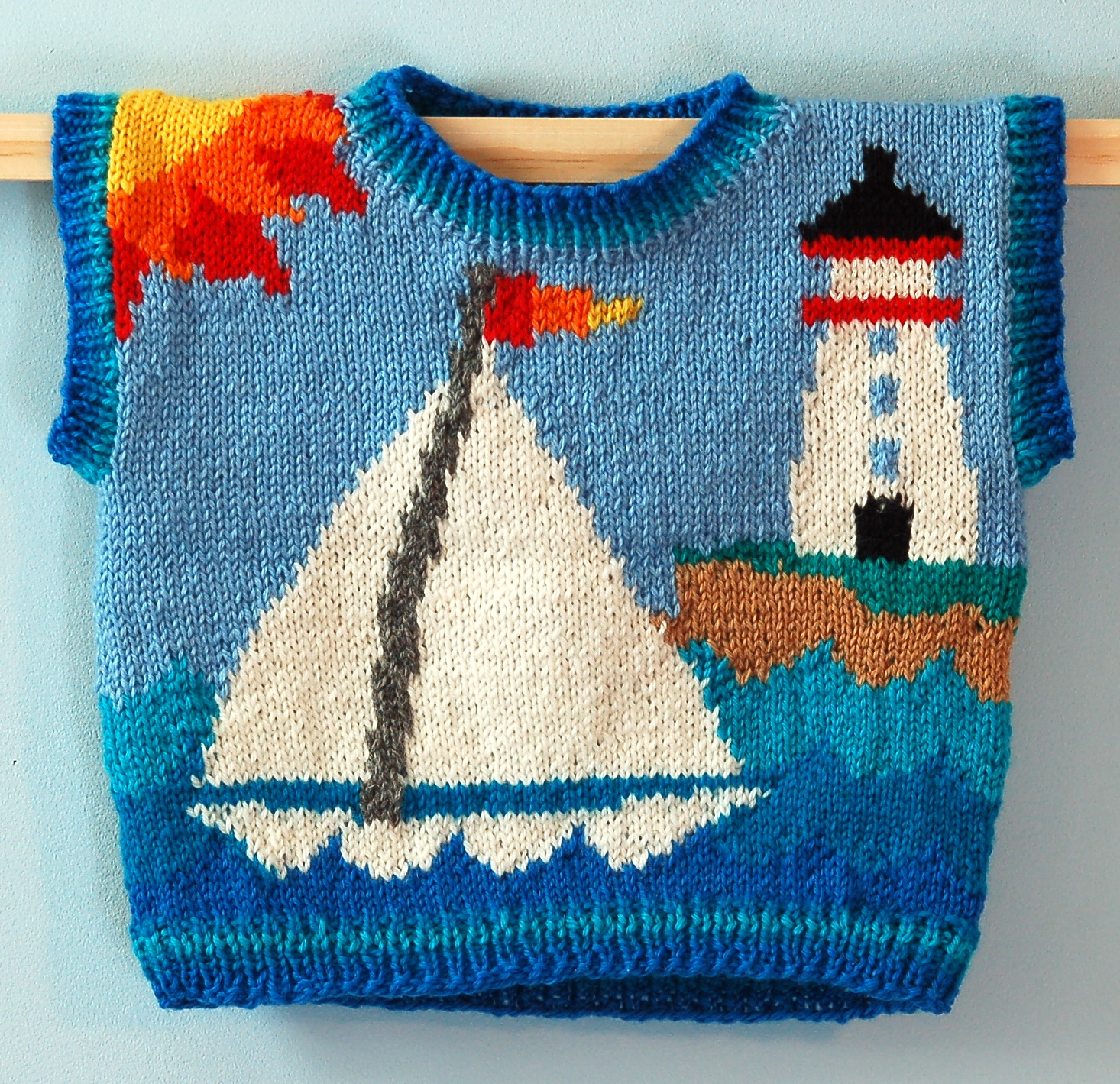 ONE YEAR: LIGHTHOUSE FRONT    On the front is a sailboat gliding past a lighthouse. On the back is a tugboat. The sun and island are continuous. The ribbing at the neck, armhole openings, and hem is shades of blue.
