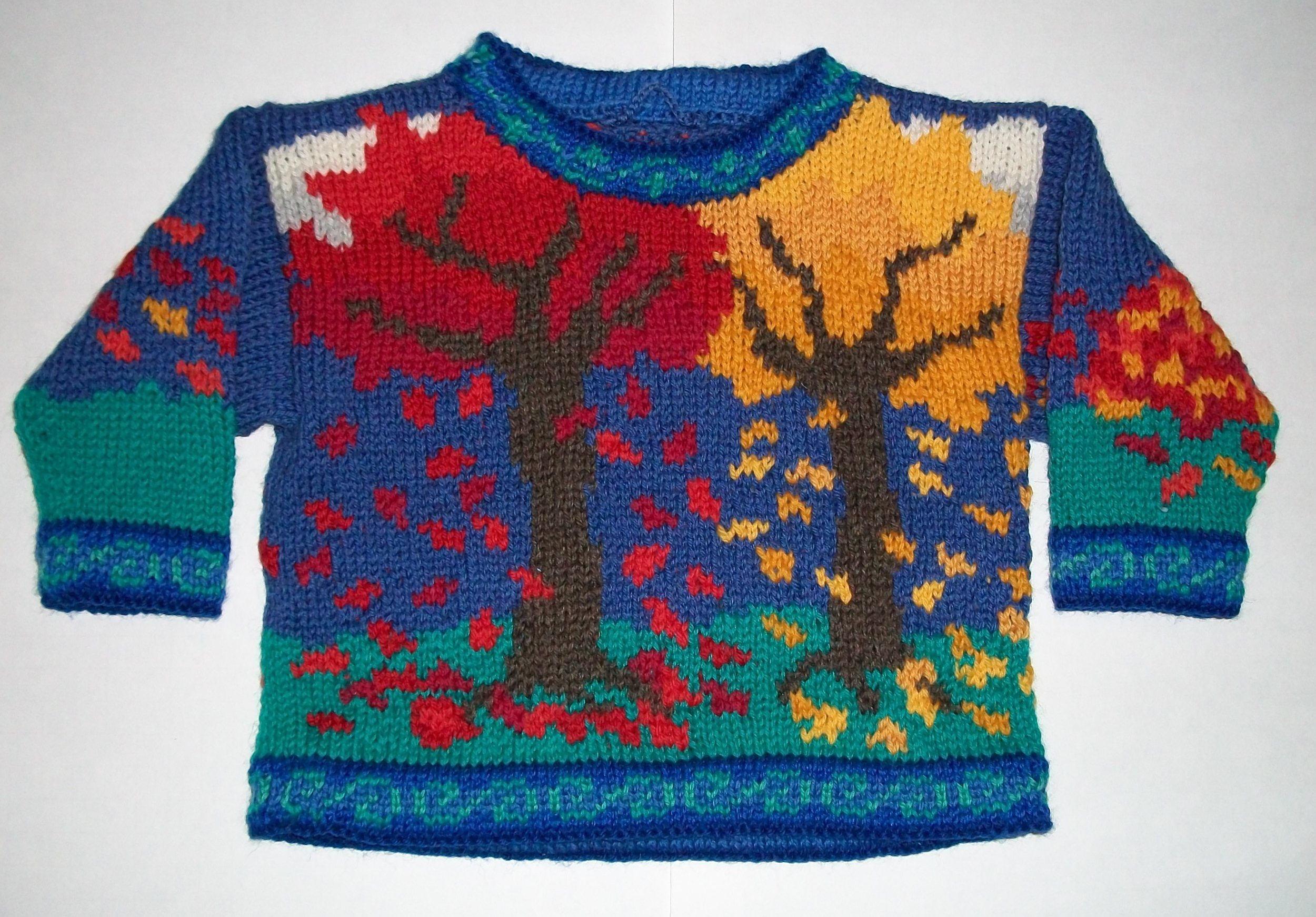 ONE YEAR: FALLING LEAVES FRONT    On the front are two autumn trees losing their leaves in the wind. On the back a pile of leaves is forming. The right and left sleeves also have piles of leaves in shades from red to gold. The neck, wrists, and hem trim is turquoise swirls on dark blue.