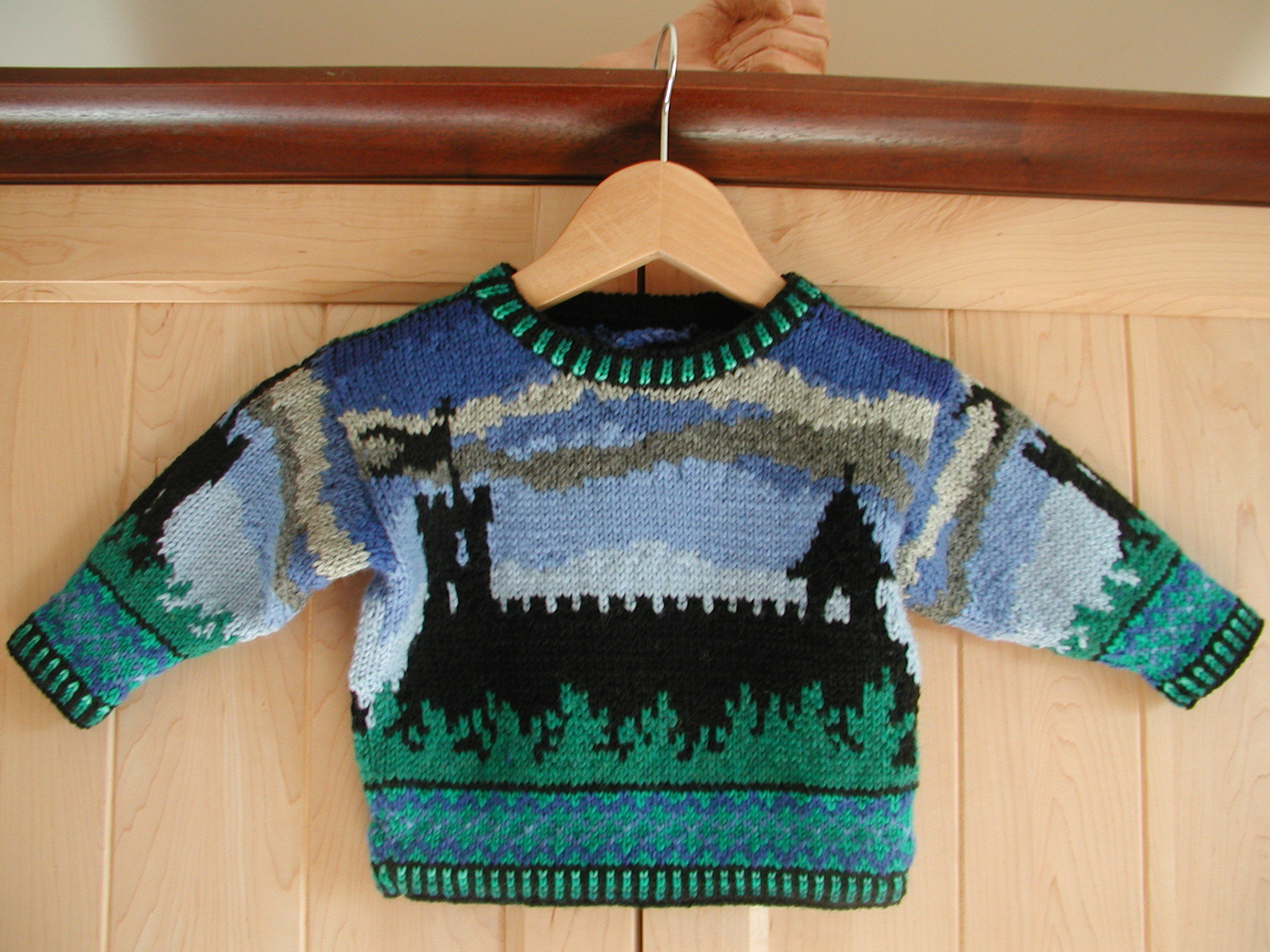 ONE YEAR: CASTLE    I have only one picture of this sweater, but the front and back are identical. A castle is silhouetted against a darkening sky. On the sleeves is a silhouetted tower. The wrists and hem trim is jagged lines of blue and green on light green. The neck, wrists, and hem trim is alternating stripes of black and greens.
