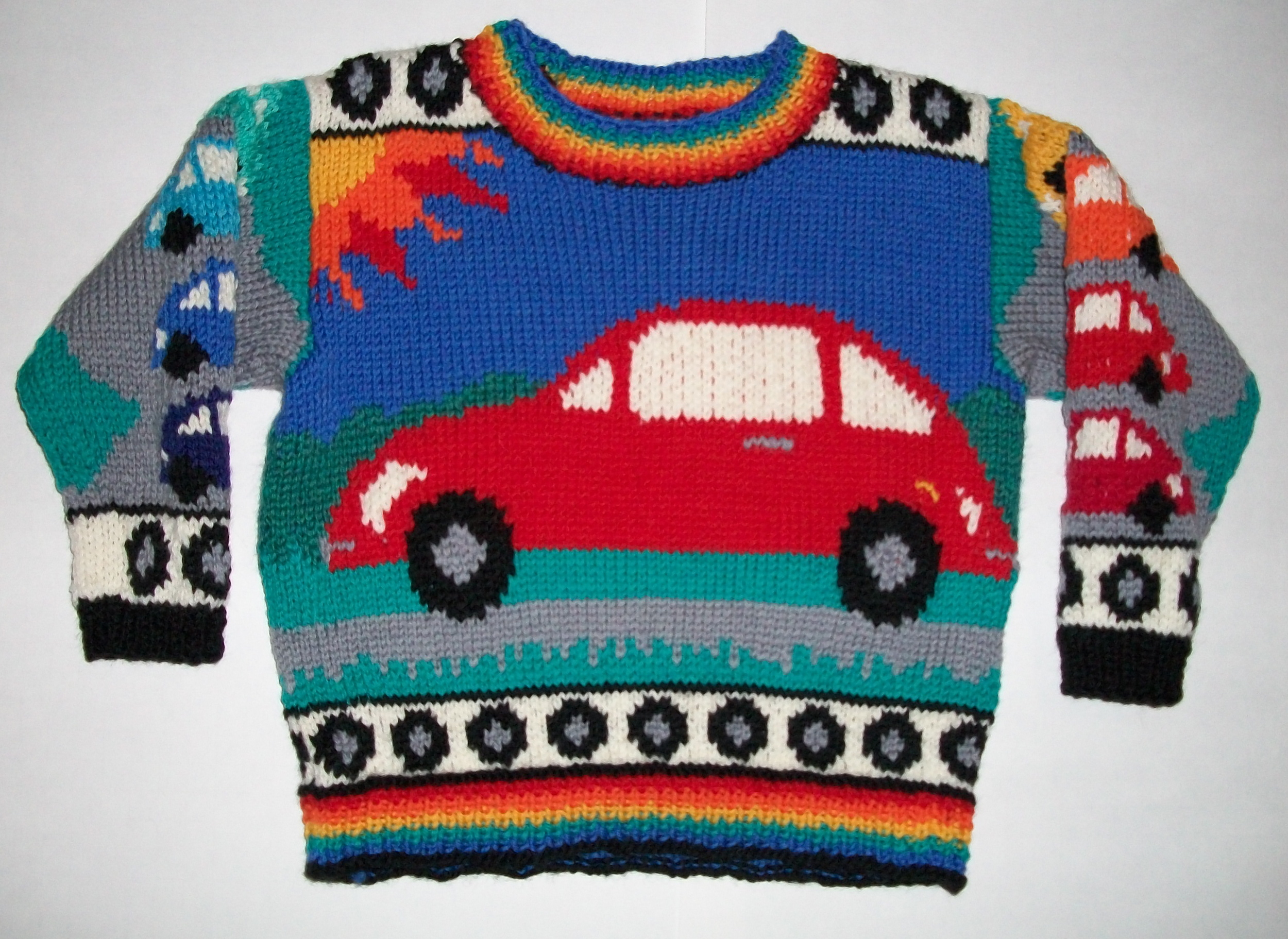 TWO YEARS: BEETLES FRONT    When Levin was two, he was obsessed with Beetle cars. On the front the car is red, and on the back the car is orange. The right sleeve has blue Beetles and the left sleeve has red to yellow Beetles. The wrists and hem trim is black and grey wheels on white. The neck and hem ribbing is rainbow rows. The wrists ribbing is black.