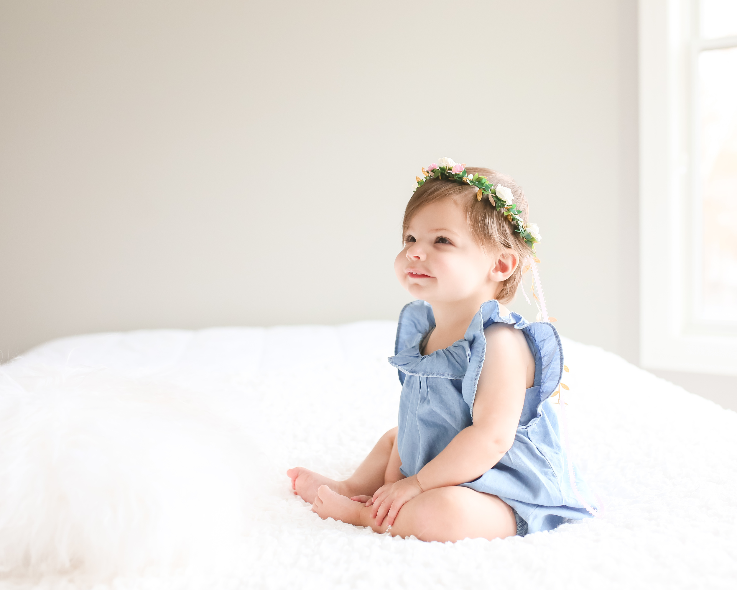 baby girl floral crown on bed