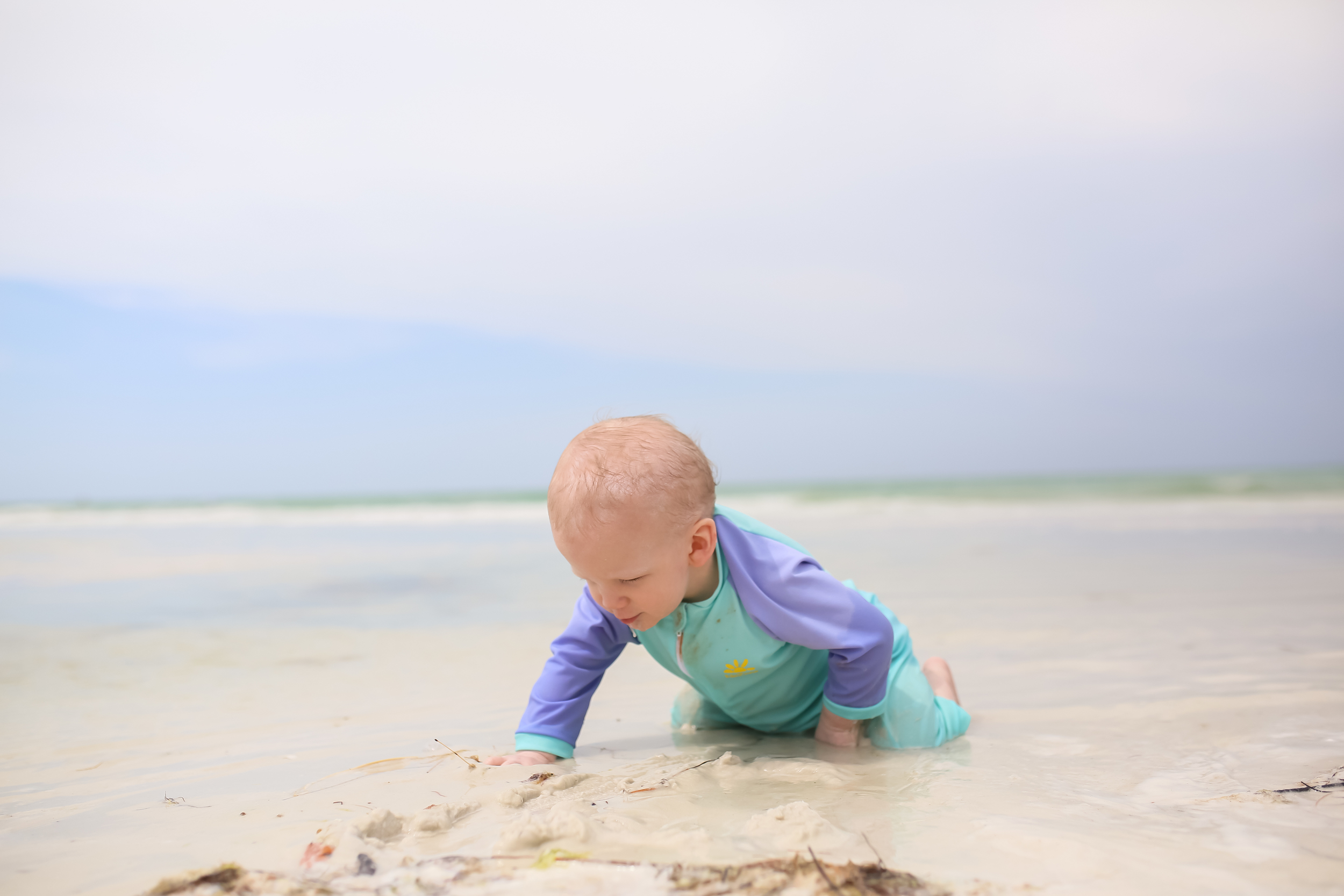 baby boy playing in sandy water