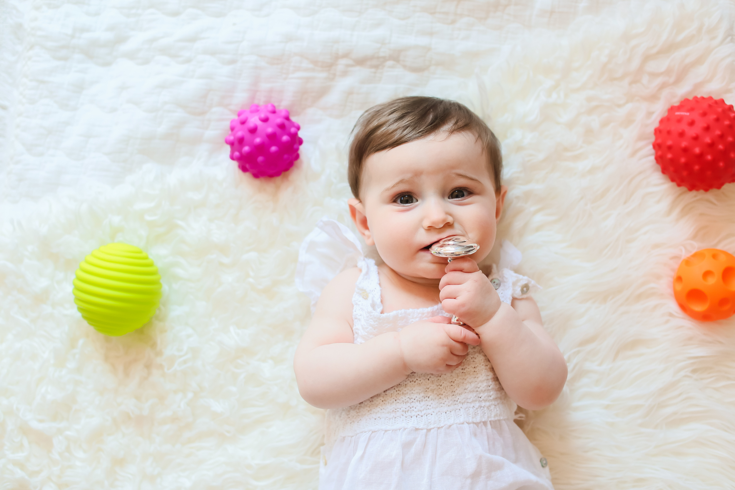 baby girl with silver rattle