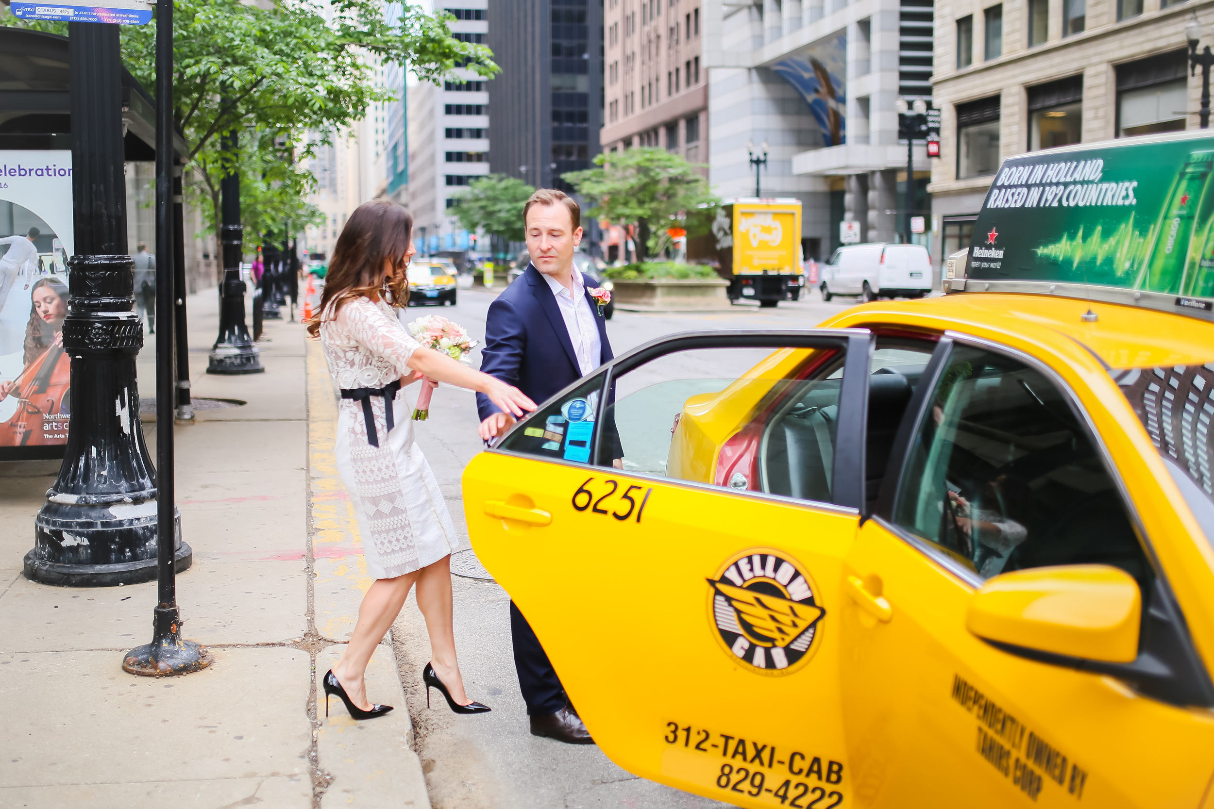 downtown chicago bride getting in yellow taxi