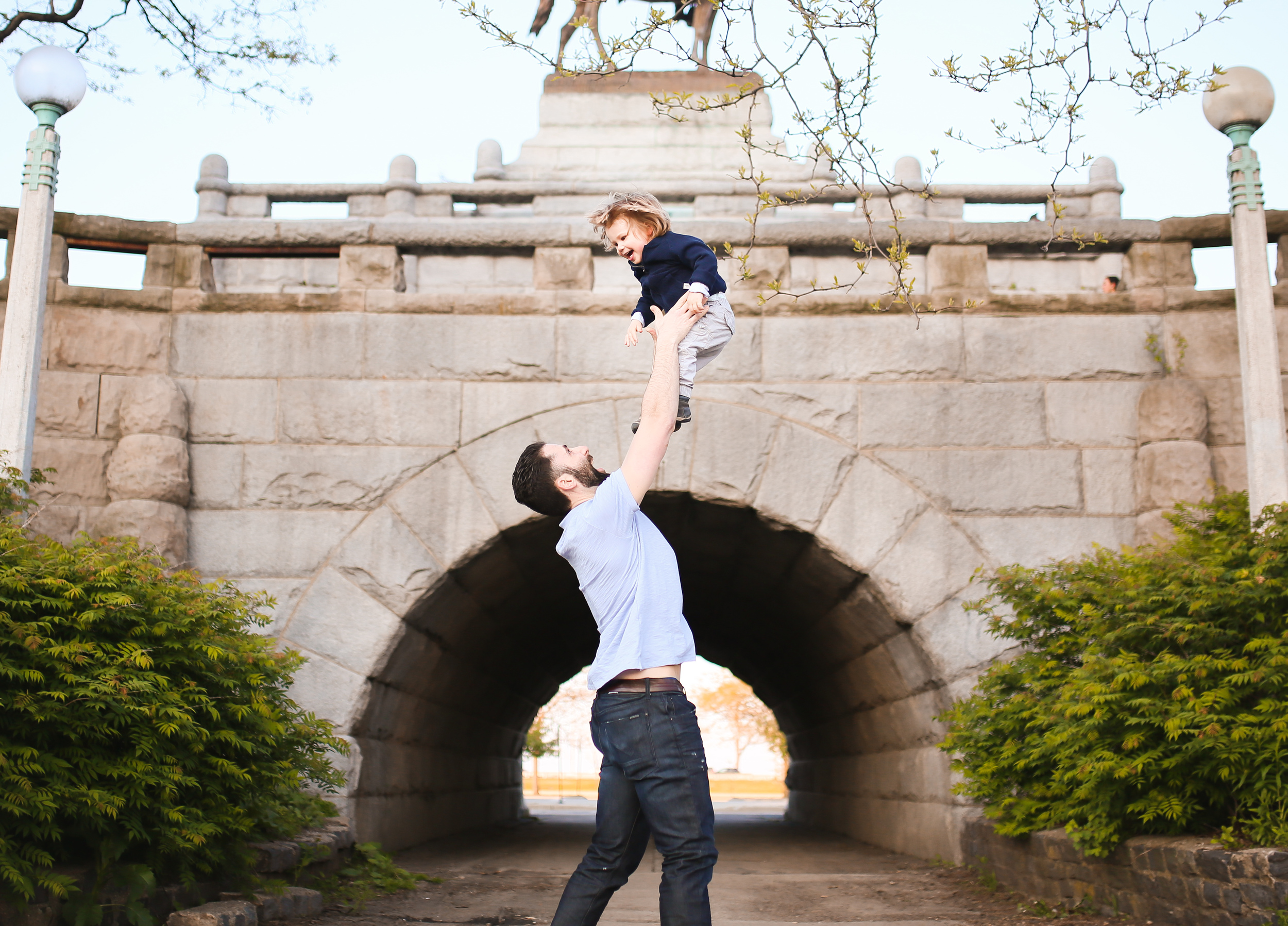 daddy tossing toddler son in air