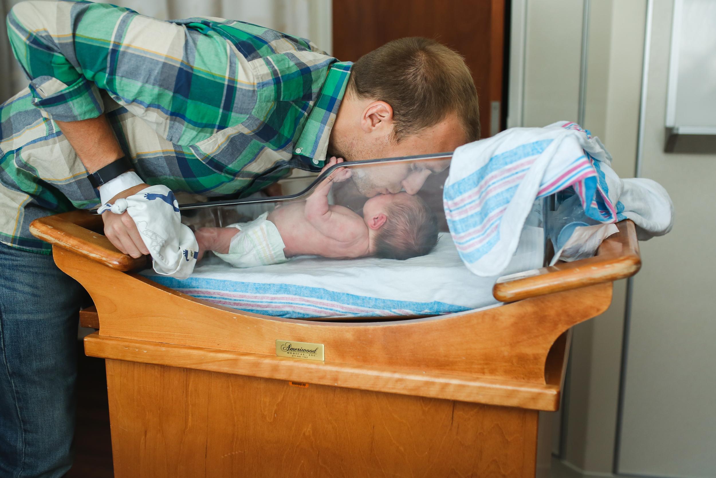 daddy kissing newborn baby