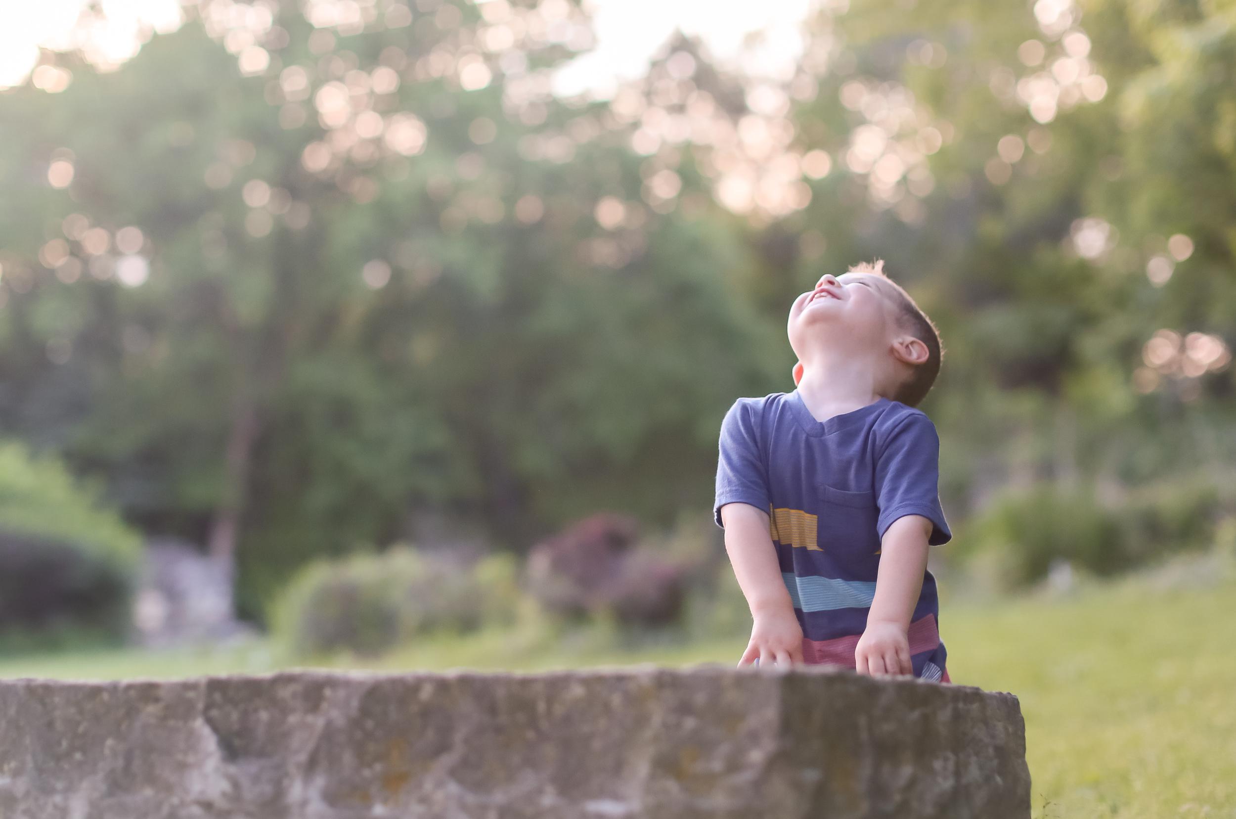 toddler boy looking up at sky