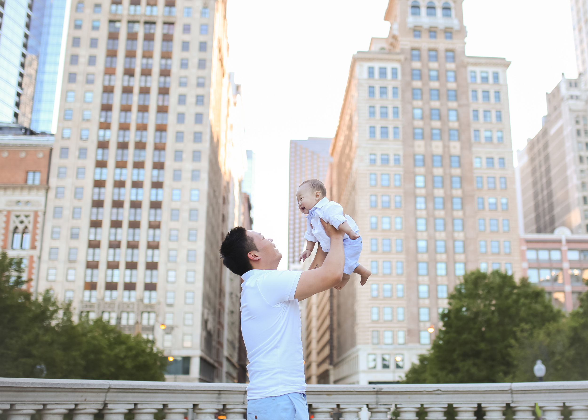 daddy son lifting in air chicago buildings