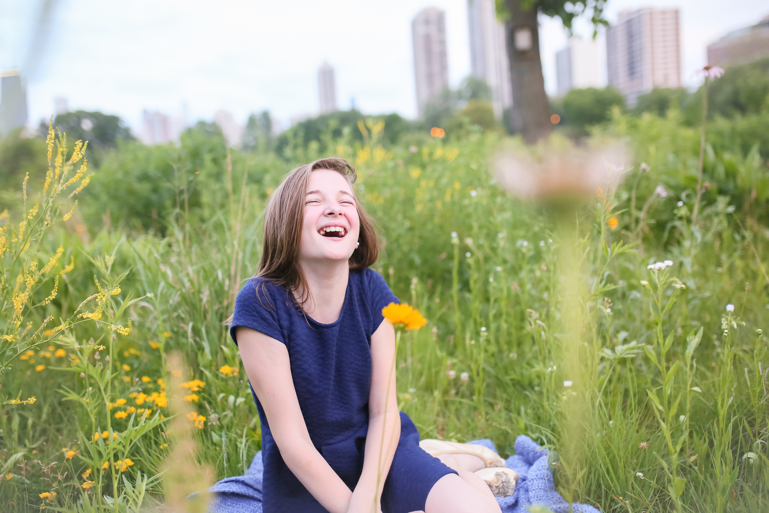 little girl laughing in field of flowers