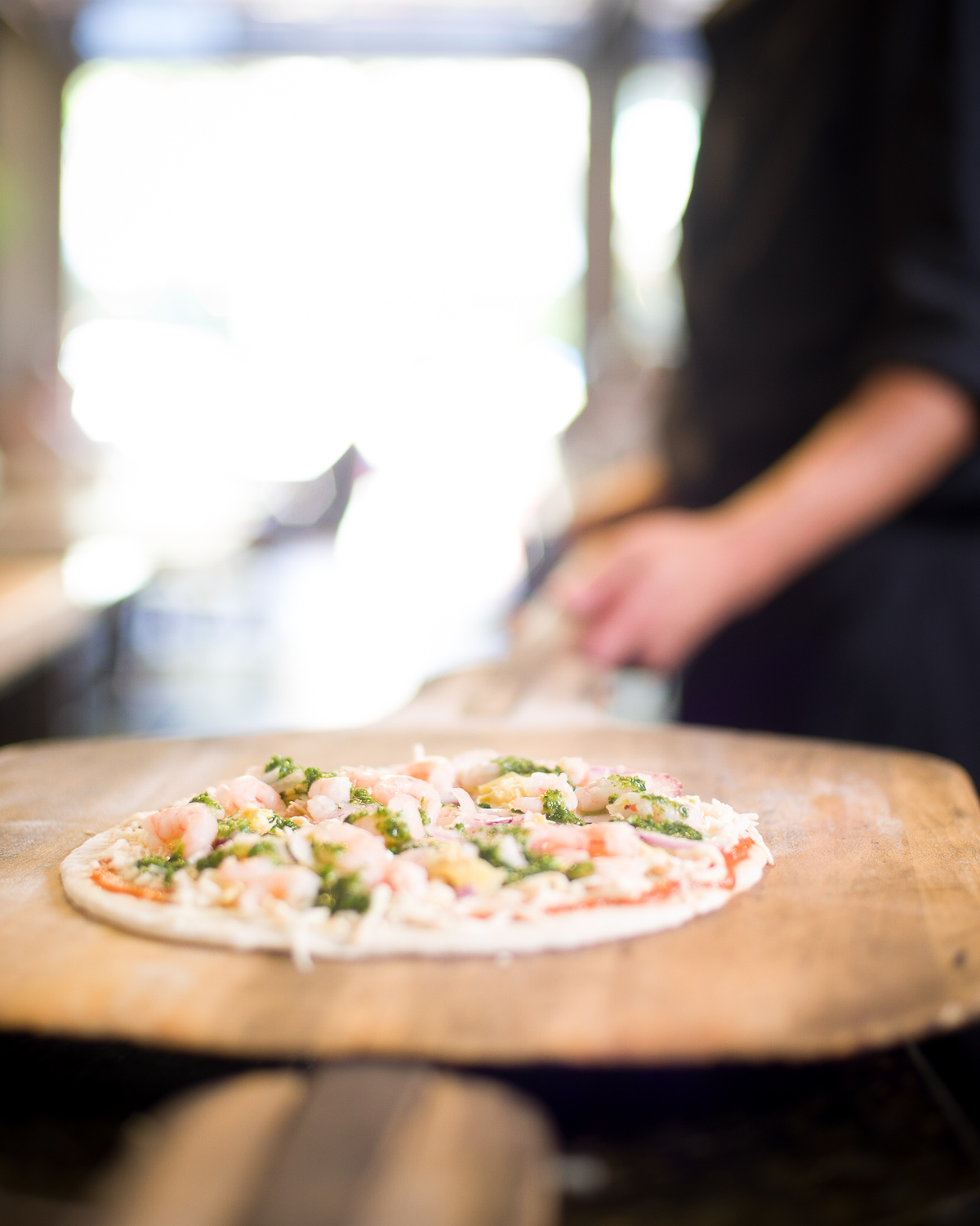 Chef holding uncooked organic shrimp pizza food photograph