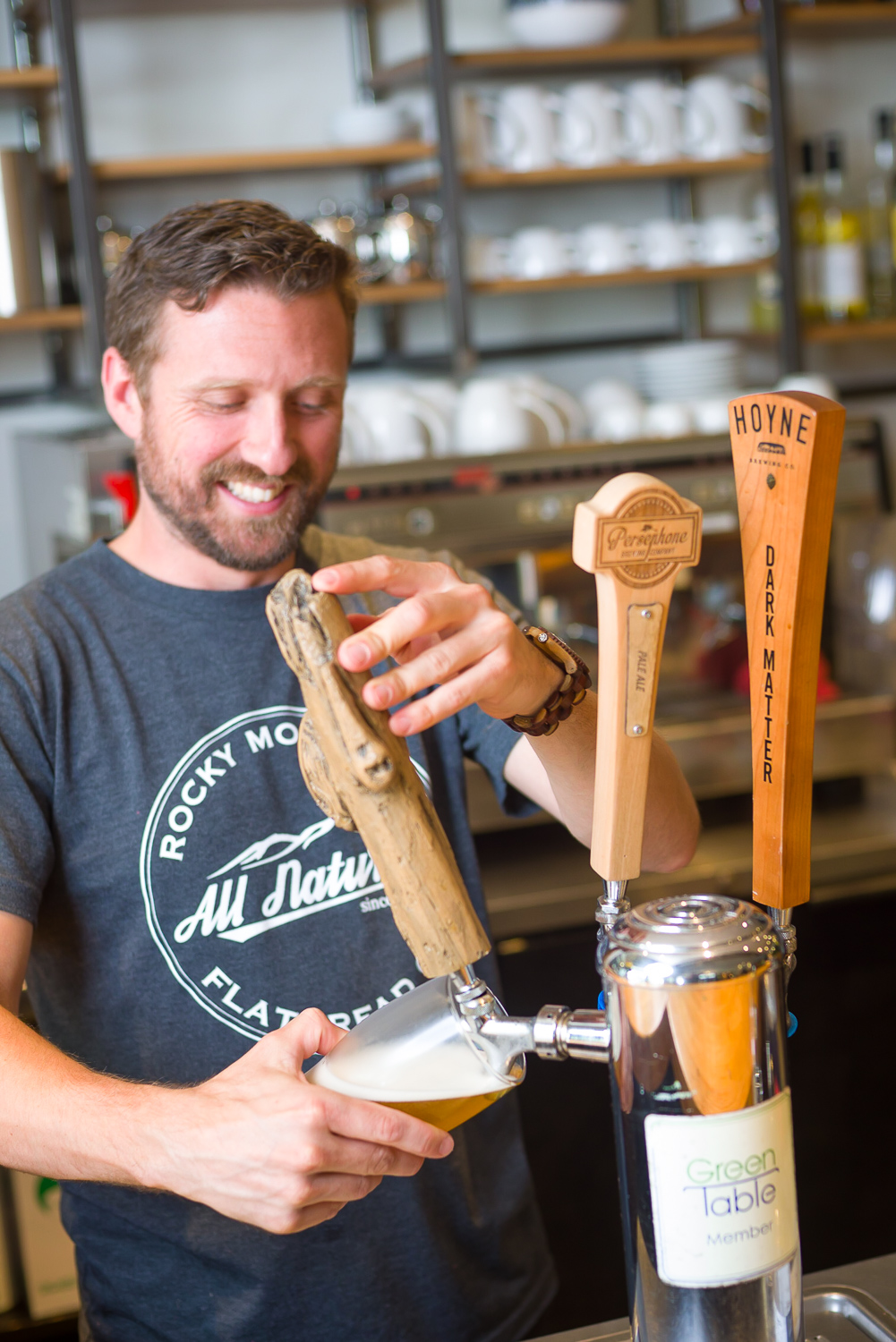 Smiling middle aged male bartender with beard pouring a beer from a tap lifestyle