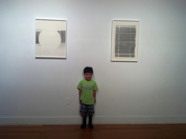 Wesley in between Claire Colette's graphite drawings at The Berkeley Art Center.