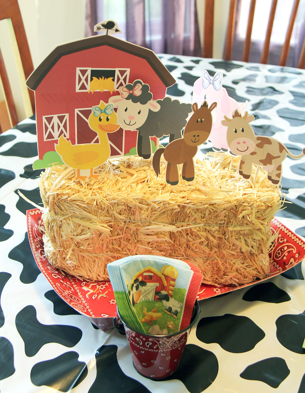 DIY Barn Themed Birthday Party Centerpiece | haybale with cut out farm animals | bandana and cow print patterns | as seen on www.gigglehearts.com