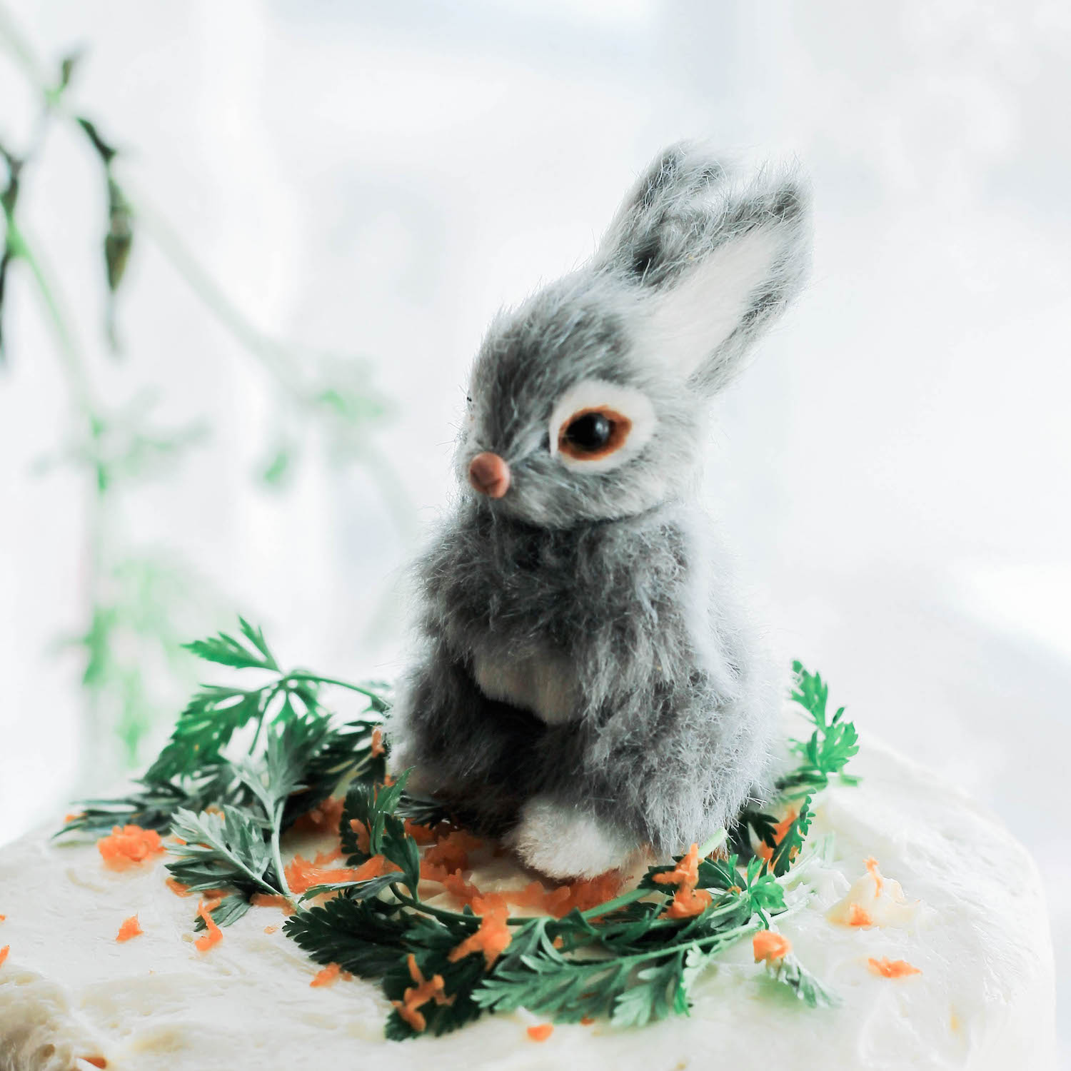 The sweetest bunny cake topper - surrounded by grated carrots and parsley sprigs / as seen in the Bunny Spring Birthday Party Inspiration Post on www.GiggleHearts.com