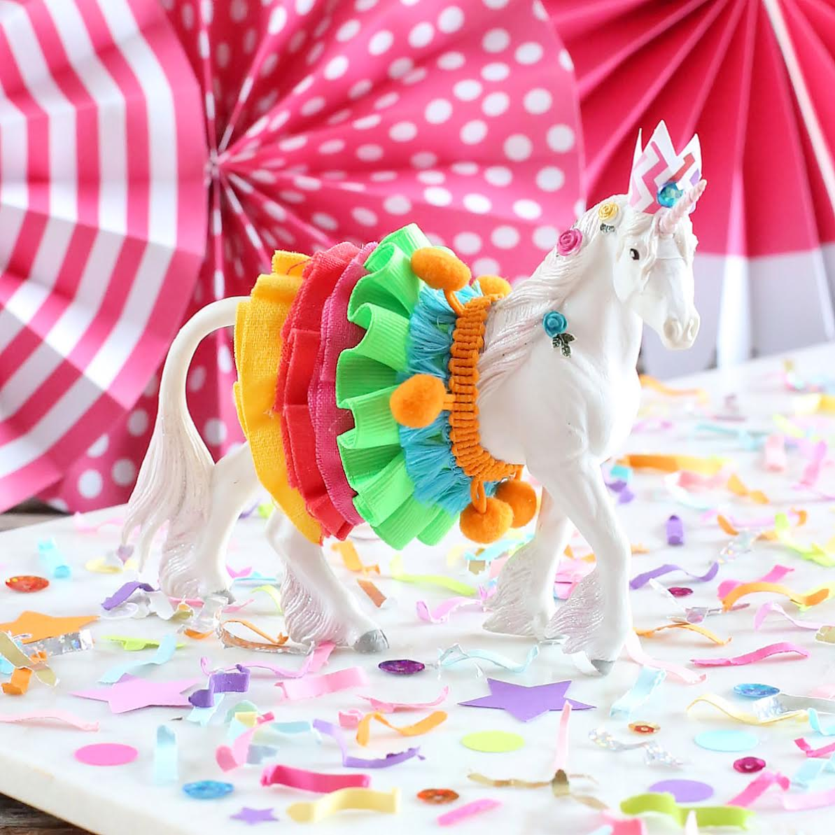 Colorful Unicorn Must-Have Party Items for a Perfectly Styled Unicorn Theme Dessert Table - a sweet Unicorn Animal Cake Topper and Festive Fetti Confetti - from The Bakers Party Shop - see more on www.GiggleHearts.com