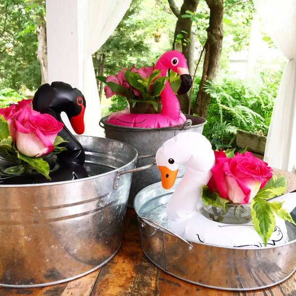 A trio of galvanized pails holds flamingo drink floaties - but instead of holding drinks, they are holding flower pots. A whimsical substitute when you don't have a pool - for the Flamingo Outdoor Movie Party from Lori of Giggle Living - as seen on www.GiggleHearts.com