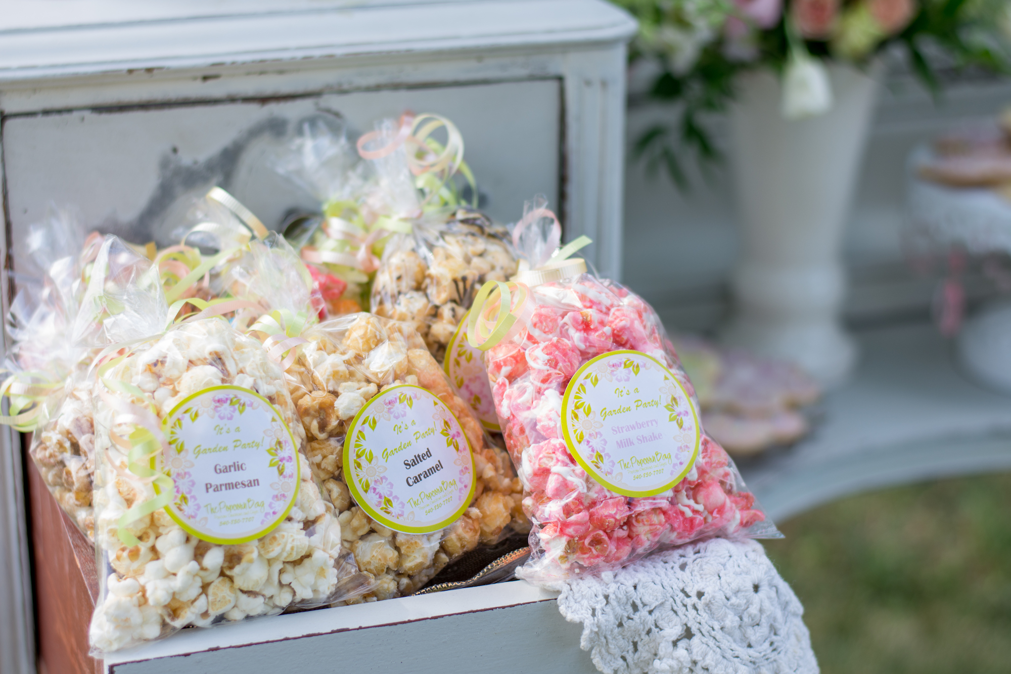 Vintage Garden Birthday Party Favors - Flavored Popcorn in Bags with Personalized Labels / Outdoor Garden Party / Present Party Favors in a dresser with opened drawers / photo by Honeysuckle Rose Photography - as seen on www.GiggleHearts.com