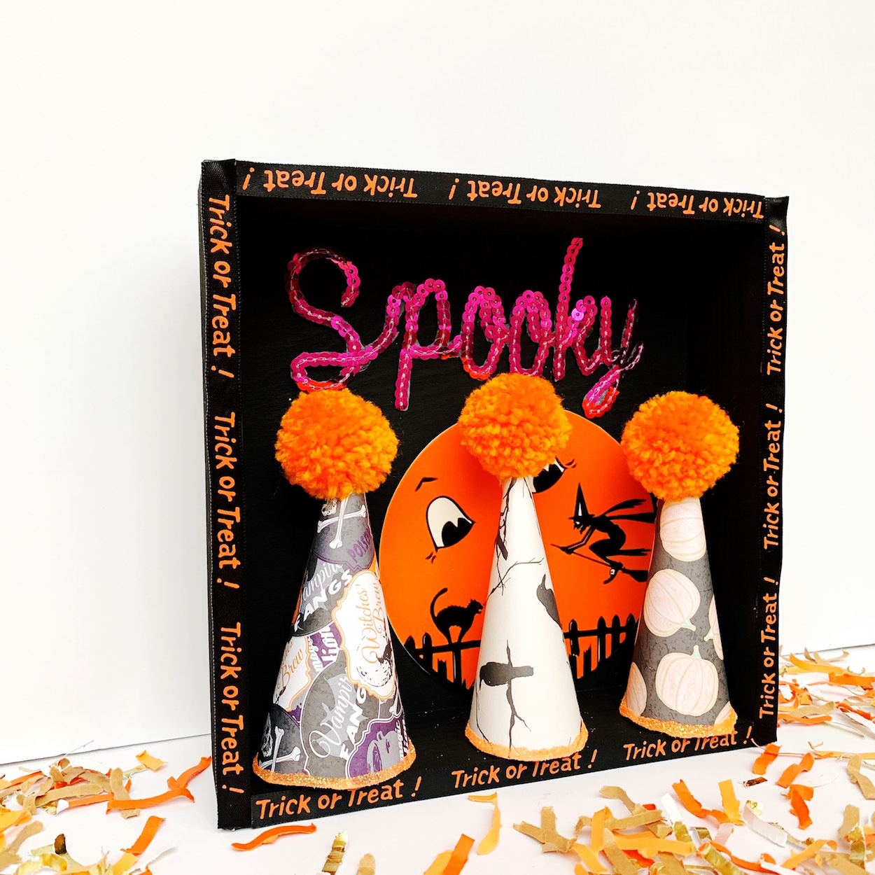 These DIY Halloween Paper Party Hats are so cute lined up in this Halloween Shadow Box with a Spooky sequin iron-on transfer. See how to create this Halloween Mantle Decor on Giggle Hearts www.gigglehearts.com #halloweendecorations #halloween #halloweencrafts #diycrafts #halloweendecor #partyhats