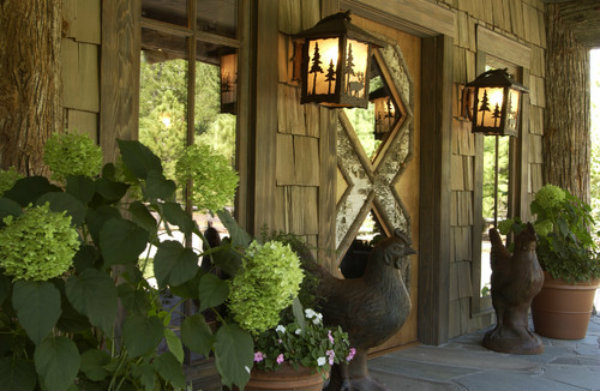 Gabbers Design Studio brought this front porch oasis to life with greenery, a pair of statuesque hens and two sconces displaying an organic motif from our Log & Timber collection.
