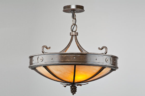 A simple grape motif on the finial of this dome light creates a timeless look for the tasting room of a wine cellar.