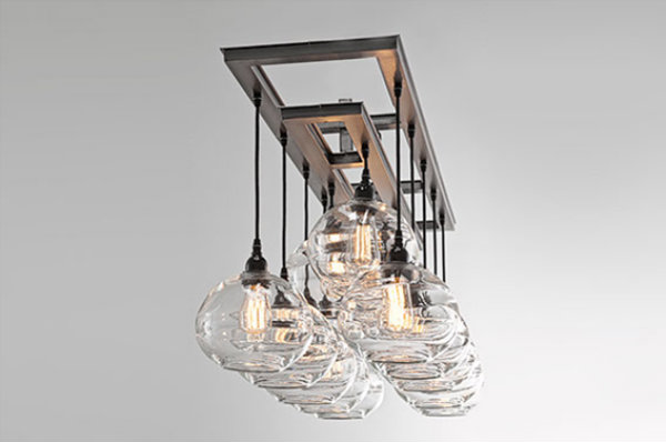 Reflective qualities make this stunning Bolla dining light highly functional. Each bulb is encased in a concave optical glass shade and is suspended from a rectangular base. The blown glass shades give the fixture a shimmering quality and a subtly organic aesthetic.